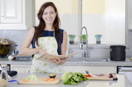Young beautiful woman cooking a recipe from a book Stock Photo