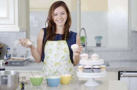 Cute young woman decorating some cupcakes Stock fotó