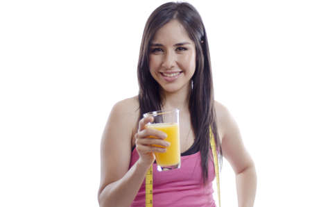Young beautiful woman in sporty outfit drinking orange juice