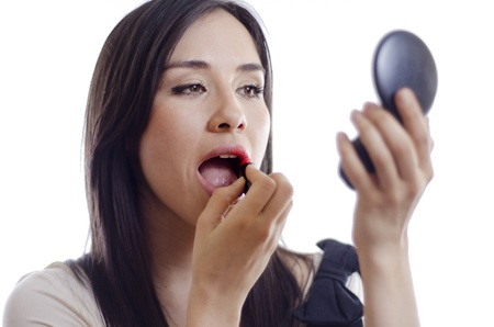 Young beautiful woman putting on some lipstick and looking at her hand mirror photo