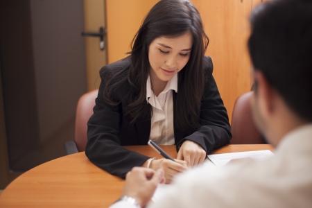 美しい若い女性は文書の署名