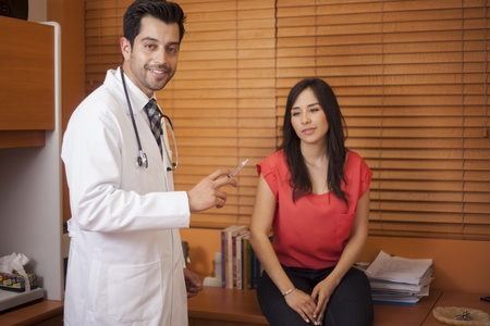 flu shot: Handsome young doctor giving a vaccine to a female patient Stock Photo