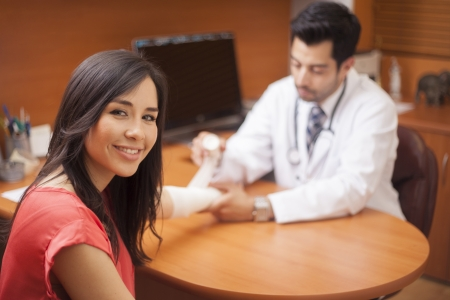 broken arm: Beautiful woman getting an arm cast at the doctor s office Stock Photo
