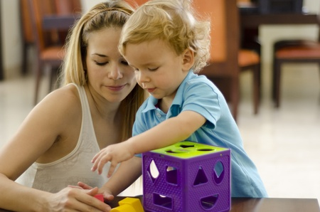 Young mother and son solving a puzzle together Stock Photo