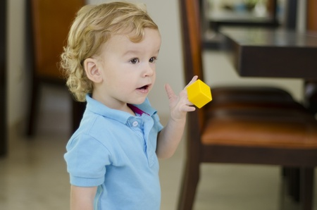 Cute boy holding a piece to a puzzle and showing it to someone Stock Photo