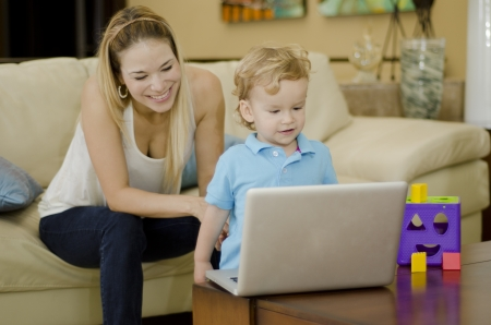 Young mother and her son having fun and learning with a laptop at home photo