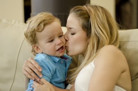 mom kiss son: Cute young mother kissing her son on his cheek