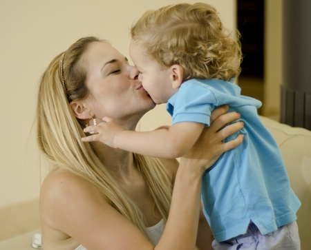 mom kiss son: Young beautiful mother holding her son and kissing him in the mouth