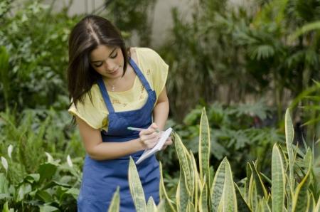 taking inventory: Cute female gardener working on inventory
