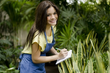 taking inventory: Cute female gardener working on inventory and smiling