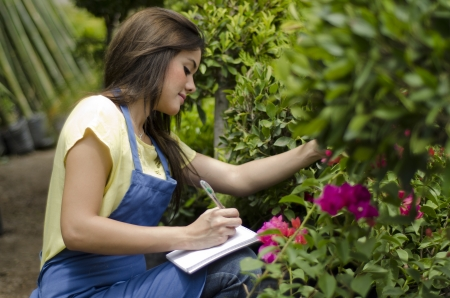 taking inventory: Young female gardener taking notes and doing inventory at work