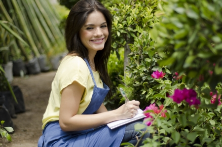 taking inventory: Beautiful female gardener taking notes and doing inventory at work Stock Photo