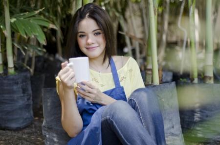 break: Cute young gardener taking a coffee break from work at a nursery garden