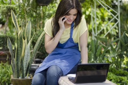taking inventory: Cute female gardener taking a note from a customer on the phone Stock Photo