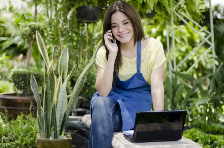 taking inventory: Cute female gardener talking to a customer on the phone
