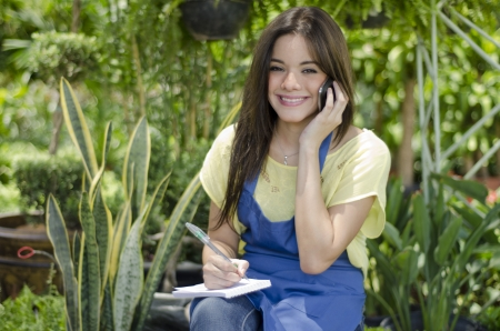 taking inventory: Cute female gardener taking an order from a customer on the phone Stock Photo