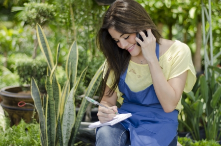 taking inventory: Young female gardener taking an order from a customer on the phone Stock Photo