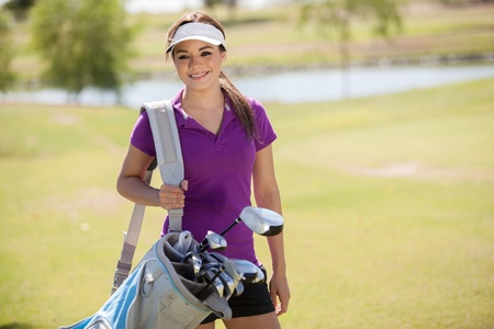 Cute young Hispanic woman carrying a golf bag and smiling