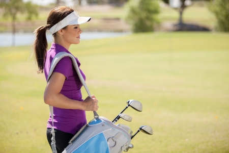 Beautiful female golfer carrying a golf bag and looking towards copy space photo