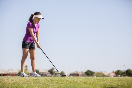 woman golf: Beautiful young golfer with copy space about to hit the ball