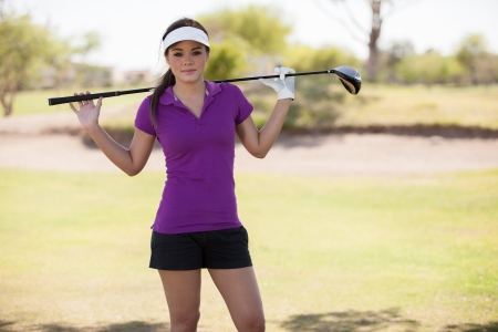 Portrait of a cute young woman holding a golf club photo