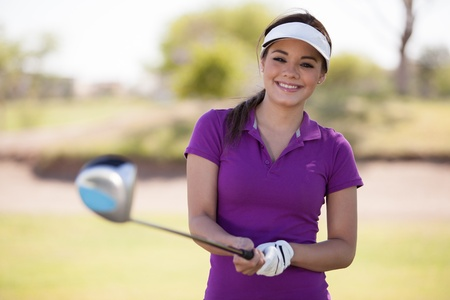 Cute Hispanic female golfer holding a golf club with both hands and smiling photo