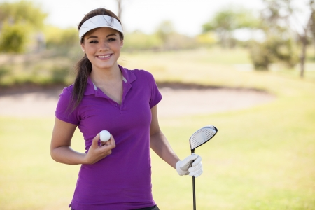 Beautiful young woman holding a golf ball and a club and smiling photo