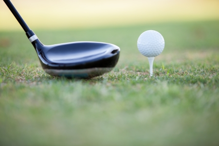 Closeup of a golf club and a golf ball ready for tee off photo