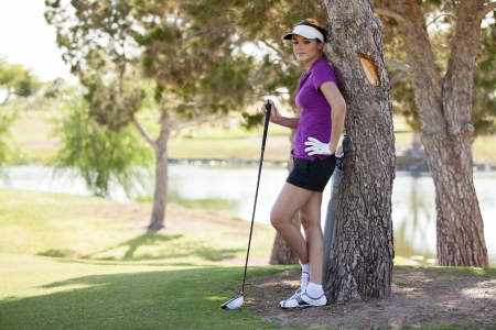 Latin female golfer resting under a tree on a sunny day Stock Photo - 19382937