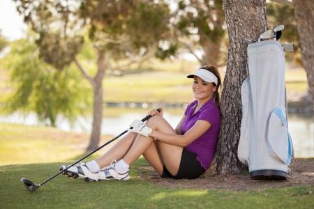 Beautiful Hispanic female golfer taking a break and sitting under a tree photo