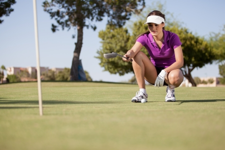 woman golf: Beautiful female golfer planning how to get the ball in Stock Photo