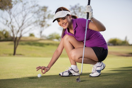 Beautiful young woman trying to cheat at golf photo