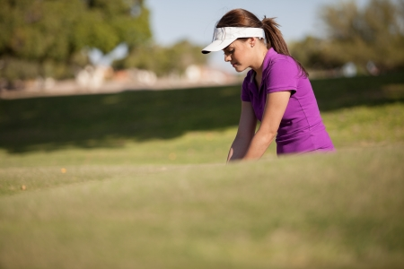 Gorgeous female golfer inside a trap focusing on her shot photo