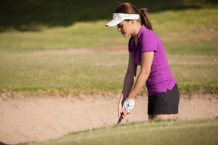 Hispanic female golfer focused on getting her ball out of a sand trap photo
