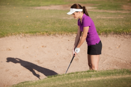 Cute female golfer attempting to shoot a ball out of a sand trap Stock Photo - 19382924