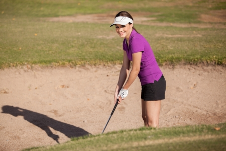 Beautiful young woman trying to get out of a sand trap in a golf game photo