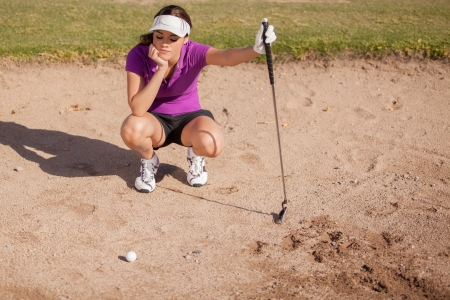 traps: Young female golfer frustrated and stuck in a sand trap Stock Photo