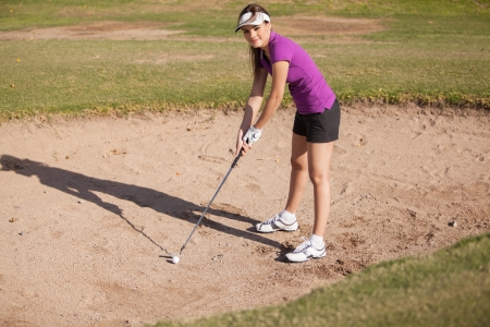 Cute Hispanic female golfer trying to get her ball out of a sand trap photo