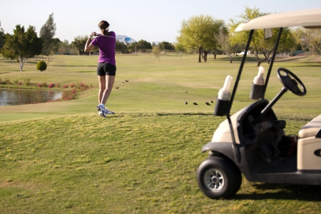 Young female golfer teeing off next to a golf cart photo