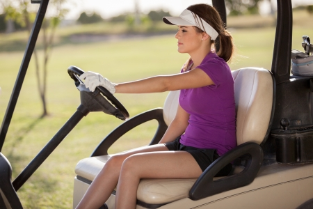 Beautiful young woman driving a golf cart on a sunny day photo