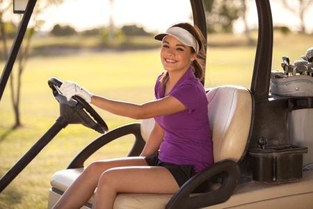 Cute Hispanic female golfer driving a golf cart and smiling Stock Photo - 19382887