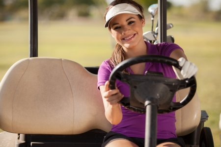 Beautiful young woman driving a golf cart and smiling photo