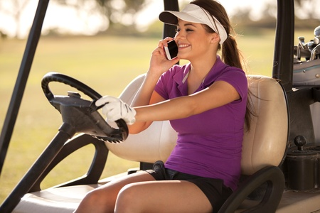 Pretty female golfer talking on the phone while driving a golf cart photo