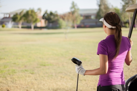 Young female golfer looking at the golf course with copy space photo
