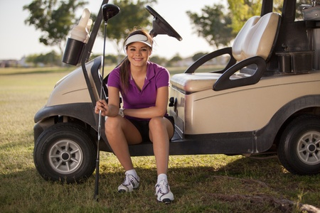 Beautiful Latin golfer sitting in a golf cart and smiling photo