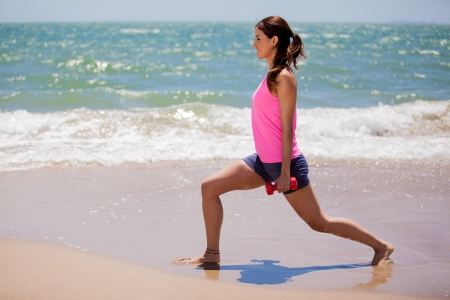 Pretty young woman in sporty outfit lifting some weights at the beach Stock Photo