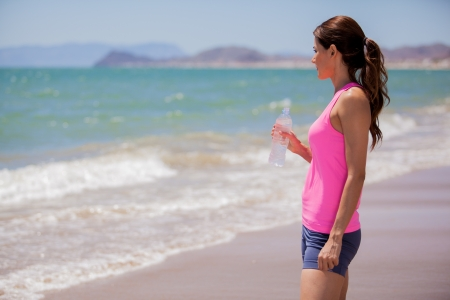 Pretty Hispanic brunette taking a break from running and drinking water from a bottle photo