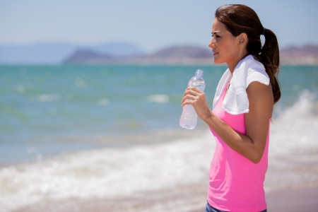Beautiful young woman taking a water break from running while looking at the ocean photo