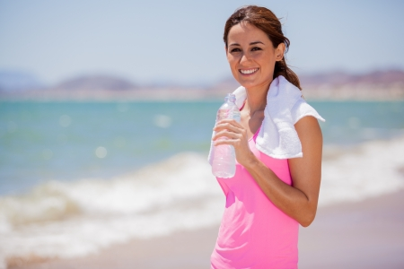 Beautiful young brunette drinking water and cooling off after running at the beach photo