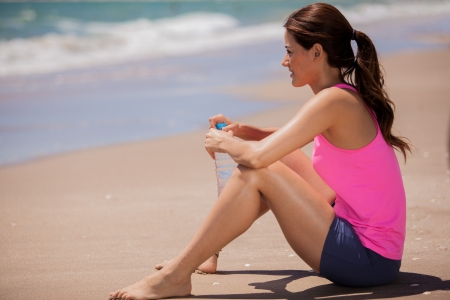 Happy Latin woman taking a break to drink water after jogging at the beach photo